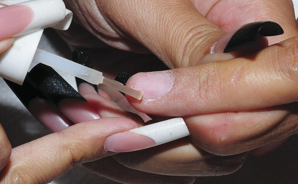 Match the tip to the natural nail. The tip should fit from side to side of the natural nail, within the finger's lateral sidewalls. Place a small amount adhesive to the white tip. Be sure, you spread the adhesive even, also to the corners.